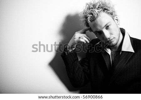 BW portrait of handsome stylish blond man in suit pointing finger at his head