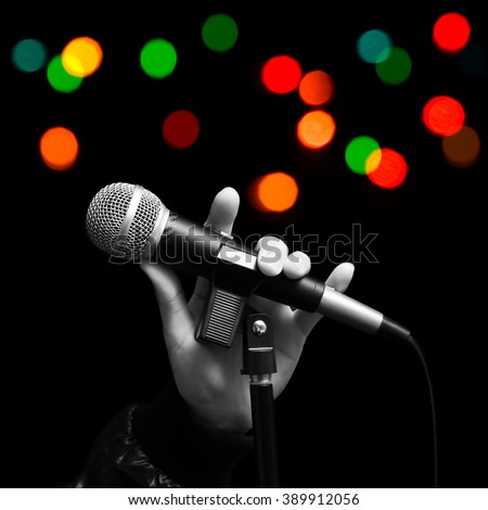 BW singer left hand holding dynamic microphone with colourful bokeh. ( hand sign mean love ) concept = love to sing