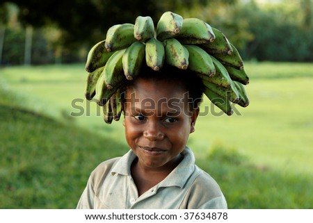 BWAGAOIA, PNG - JULY 12: Unidentified melanesian child transporting bananas on head. July 12, 2009, Bwagaoia, Misima Island, Papua New Guinea