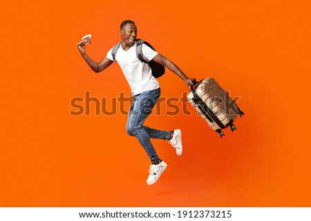 Bye-bye, Im going vacation. Young happy black man with suitcase, backpack, passport and flight tickets jumping up orange studio background. Excited african american guy running and looking back Photo stock ©
