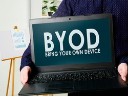 BYOD bring your own device. A man holds a laptop in his hands.
