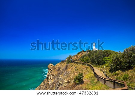 Byron Bay Lighthouse Framed Against Blue Sky With Hang Glider in Distance