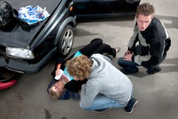 Bystander providing first aid to an injured woman lying on the ground, bleeding, after a car crash, with a first aid kit on the hood of her damaged car