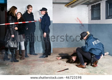 Bystanders being held at a distance by a police man at a murder scene, with a police woman tending to the victim