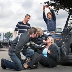 Bystanders checking up and providing first aid to an injured bleeding driver after a car crash. A man is taking pictures