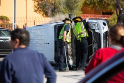 Bystanders watching two emergency reponders working on a rolled over minivan
