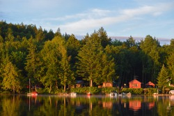 Cabin coastline on Saranac Lake in upstate New York bathed in the morning sunrise. The colored cabins are reflected in the water