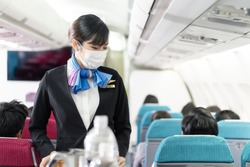 Cabin crew pushing service cart and serve to customer on the airplane during flight. New normal, flight attendant and all passengers wearing face mask to prevent COVID infection during virus pandemic.