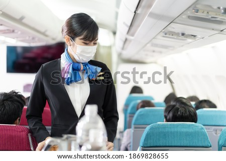 Cabin crew pushing service cart and serve to customer on the airplane during flight. New normal, flight attendant and all passengers wearing face mask to prevent COVID infection during virus pandemic. Photo stock ©