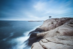 Cabin on cliff near sea with dramatic sky