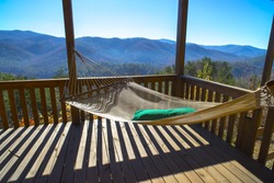 Cabin vacation. Cabin getaway. Hammock at terrace in a cabin. View of blue mountains and blue sky at autumn sunny day. Rest and relax in house in the mountains at fall. Blue Ridge, GA, USA