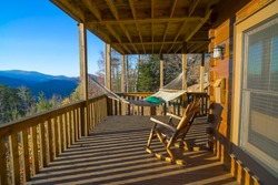 Cabin vacation. Hammock and rocking chair on terrace at cabin. View of blue mountains and blue sky. Rest and relax in the mountains at fall. Wooden house at Blue Ridge mountains, GA. Cabin getaway.