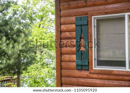 Cabin window shutters green pine tree cutouts wood close up background house north woods forest