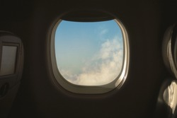 Cabinet airplane window with blue sky outside