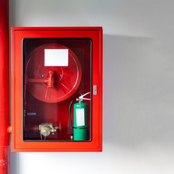 Cabinets of fire protection set is settled with the Emergency Fire Extinguisher and Rolled Pipe