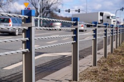 Cable barrier, also called guard cable or wire road safety barrier, is increasingly used road safety. Close-up of steel ropes.