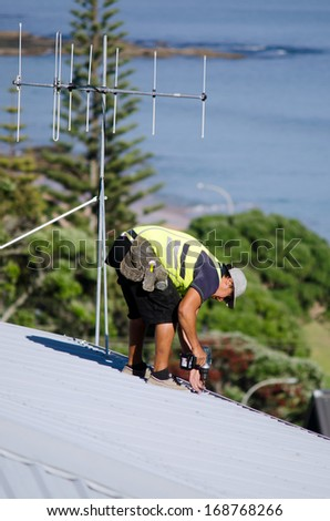 CABLE BAY,NZ:Roofer fixing a roof on Dec 12 2013. In 2000, 717 workers died of injuries caused by falls from ladders, scaffolds, buildings, or other elevations.