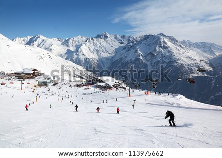 Cable car, buildings in mountains. Many skiers ride in Alps at sunny winter day.
