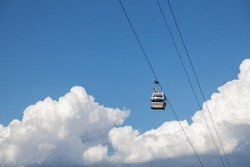 Cable car cabin over blue sky with clouds. Cableway, green transportation. Tbilisi. Georgia.