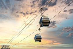 Cable car cabins against amazing sky and clouds. Cableway, green transportation.