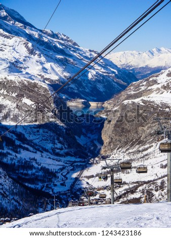 Cable car on the background of an alpine village and an alpine lake on a clear, fine, winter day in Tignes, Alps, France