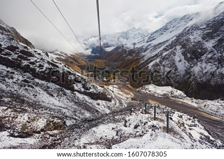 Cable car on the background of mountains and clouds. Metal poles in the form of poles. Transportation of tourists in a winter ski resort.