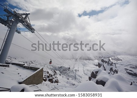 Cable car on the background of mountains, bright sunny clouds. Metal poles in the form of poles. Transportation of tourists in a winter ski resort.