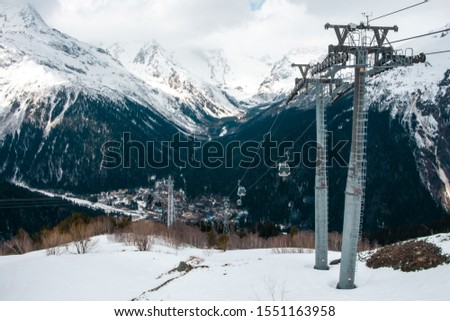 Cable car on the background of snowy mountains. Transportation of tourists in a winter ski resort. Metal poles in the form of poles.