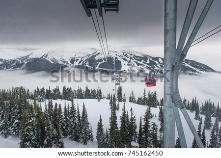Cable car running between two snow covered mountains at a ski resort #745162450