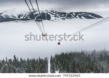 Cable car running between two snow covered mountains at a ski resort #745162465