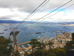 Cable car to Gibraltar rock - natural landscape rock in British Overseas Territory at southern tip of the Iberian Peninsula with view of Algeciras city in back. Panoramic view from the top.