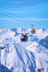 Cable cars in Hintertux Glacier ski resort in Tyrol in Mayrhofen in Zillertal valley of Austria in winter Alps. Chair lifts in Hintertuxer Gletscher in Alpine mountains with white snow and blue sky.