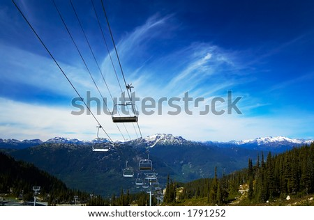 Cable carts / Gondola, pine trees, and snow peaks of Blackcomb Mountains.