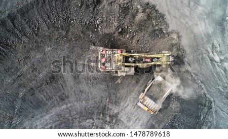 Cable excavator loads overburden from the body of a mining truck. Excavation and loading of rock mass into transport. #1478789618