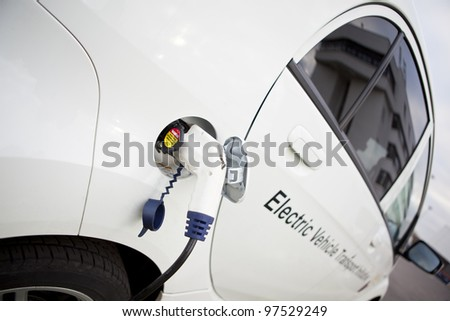 Cable hanging down from gas tank location on electrical vehicle. Outdoors