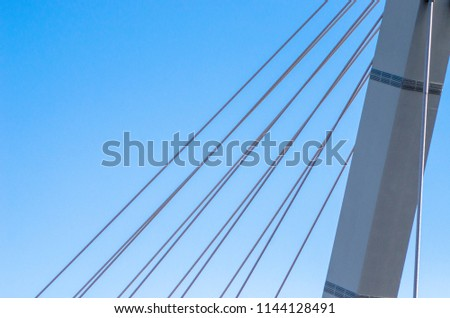 Cable-stayed bridge close-up against the blue sky. White bridge structure on a blue background. Neutral minimalistic background. #1144128491