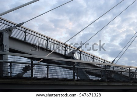 Cable-stayed bridge / suspension bridge. Contemporary urban architecture under dramatic cloudy sky. Hi-tech cityscape. #547671328