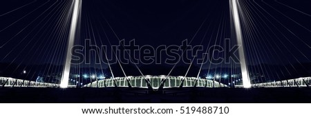 Cable-stayed bridge / suspension bridge illuminated in darkness. Modern urban architecture with electric lighting. Night contrast photo of luminous hi-tech cityscape. #519488710