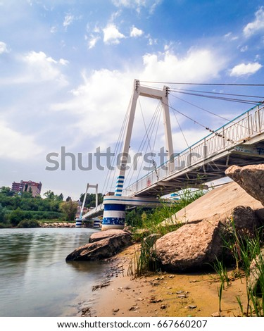 Cable-stayed suspension pedestrian bridge over the river under the blue sky with clouds #667660207