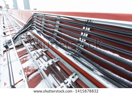 Cable tray outside with telecommunications cables, ground cables, optic fiber, power cables and transmitter data cables from antennas and outdoor remote radio units to inside equipment of #1415878832