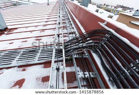 Cable tray outside with telecommunications cables, ground cables, optic fiber, power cables and transmitter data cables from antennas and outdoor remote radio units to inside equipment of #1415878856