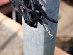 Cables or wires with bare joints. Untreated electrical wiring harnesses that are not taped in black to protect them from danger. On the background of an outdoor metal pole. Focus close and choose the