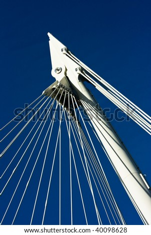 Cables supporting a footbridge in London against a blue sky