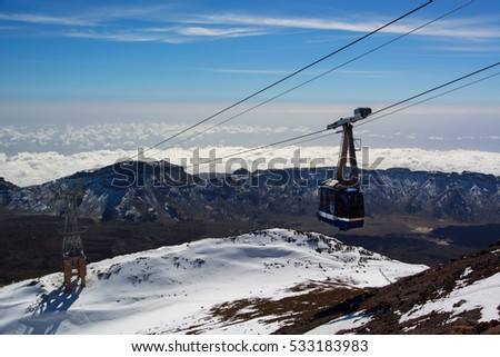 Cableway rises to the top of the volcano Teide in a sunny day  with snow and hardened lava on the mountain in Tenerife Canary island