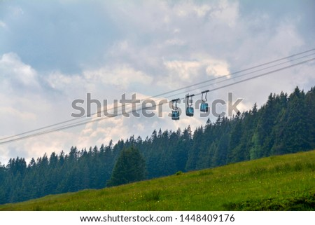 Cableway to Niederhorn station in Swiss Alps over green meadow and coniferous forest on background. Beatenberg, Switzerland