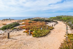 Cabo Sardão, Odemira PORTUGAL - 12 August 2019 - Footpath signposted of wood along the trail of Atlantic Ocean in the Vicentine Coast Natural Park with a man relaxing and sitting by the cliff