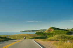 Cabot trail coastline in Cape Breton Island, Nova Scotia during the summer season. A motorcycle is visible along the road.
