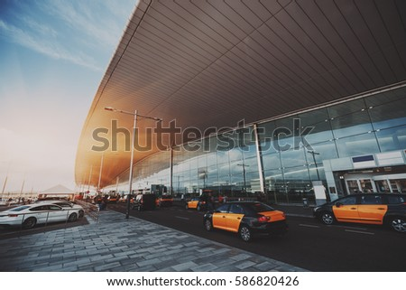 Cabstand in front of entrance of modern airport in Barcelona, cabrank with a lot of taxis near glass facade of contemporary Airport terminal in Spain with road, huge ceiling and parking lot