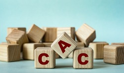 CAC (Customer Acquisition Cost) - acronym on wooden cubes on a light background. Business concept