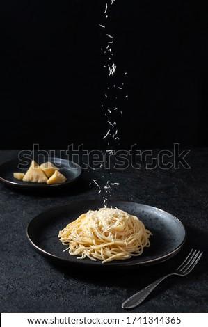 Cacio e Pepe - Italian Pasta with Cheese and Pepper. Spaghetti Sprinkled Cheese on Black Plate on Dark Background Foto d'archivio ©